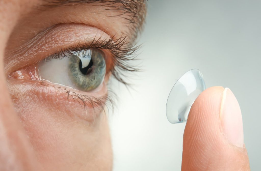 Person inserting a scleral contact lens into their eye.