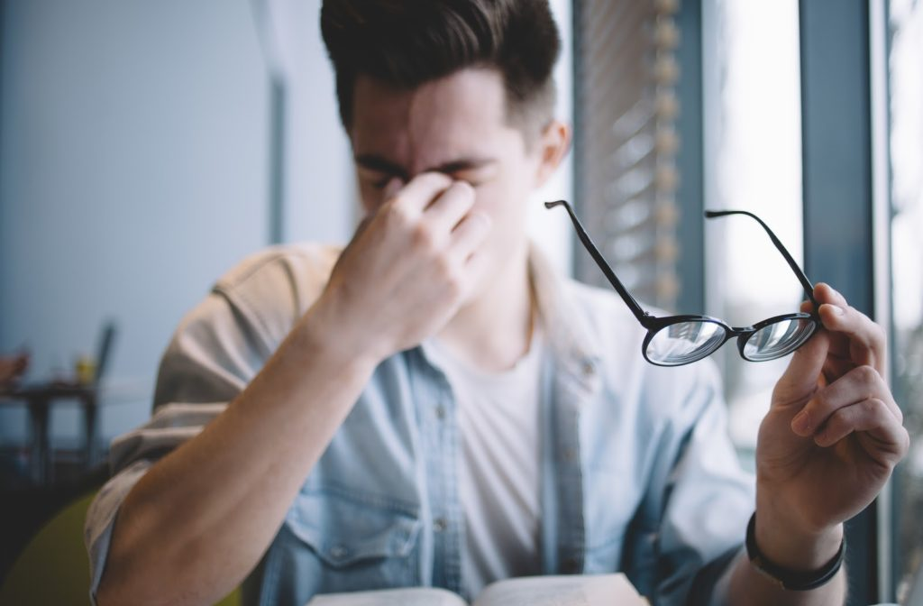 Man rubbing his eyes holding black rimmed glasses