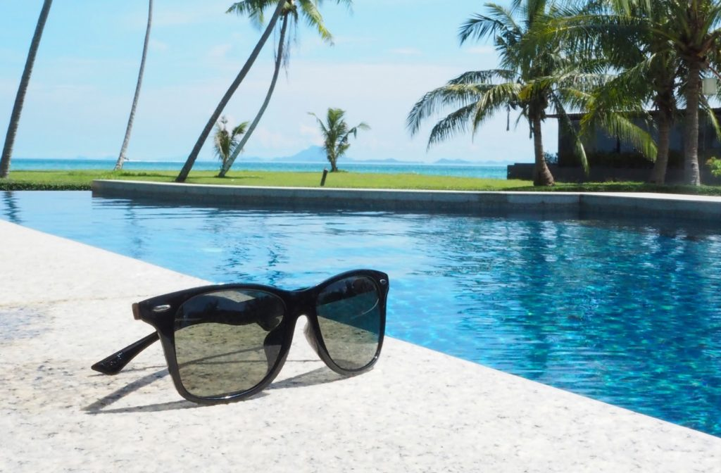 pair of sunglasses placed beside a swimming pool on a sunny day