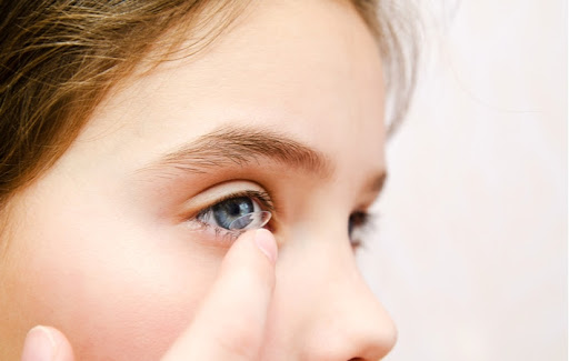 A little girl putting in multifocal contact lenses to help slow the progression of myopia
